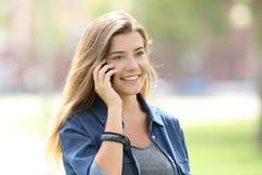 Muchacha adolescente que invita al teléfono al aire libre en un parque Fotografía de archivo libre de regalías
