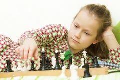 Muchacha adolescente que juega a ajedrez Imagenes de archivo