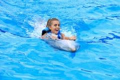 Muchacha adolescente que juega con el delfín fotografía de archivo