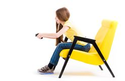Muchacha adolescente que juega con la palanca de mando en silla cómoda Foto de archivo