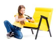 Muchacha adolescente que juega con la palanca de mando en silla cómoda Imagen de archivo libre de regalías