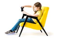 Muchacha adolescente que juega con la palanca de mando en silla cómoda Imagen de archivo