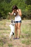 Muchacha adolescente que juega con su perrito Imagenes de archivo