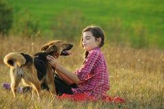 Muchacha adolescente que juega con su perro Imagen de archivo libre de regalías