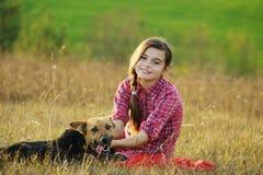 Muchacha adolescente que juega con su perro Fotografía de archivo