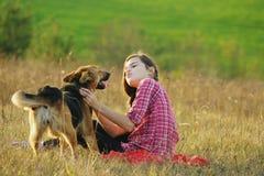 Muchacha adolescente que juega con su perro Fotos de archivo libres de regalías