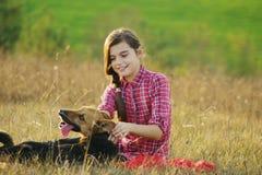 Muchacha adolescente que juega con su perro Imágenes de archivo libres de regalías