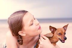 Muchacha adolescente que juega con su perro Fotos de archivo