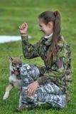 Muchacha adolescente que juega con un perrito Fotos de archivo