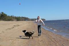 Muchacha adolescente que juega con un perro en la arena Fotos de archivo libres de regalías