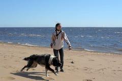 Muchacha adolescente que juega con un perro en la arena Imagen de archivo