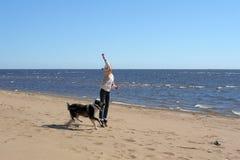 Muchacha adolescente que juega con un perro en la arena Foto de archivo