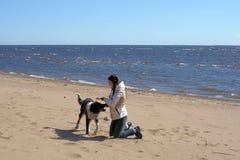 Muchacha adolescente que juega con un perro en la arena Fotografía de archivo libre de regalías