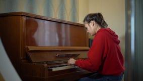 Muchacha adolescente que juega el piano viejo almacen de video