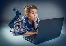 Muchacha adolescente que juega el piso en un cuaderno en gris Fotos de archivo