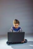 Muchacha adolescente que juega el piso en un gris del cuaderno Fotos de archivo libres de regalías