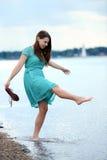 Muchacha adolescente que juega en agua en la playa Imagen de archivo