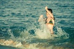 Muchacha adolescente que juega en el mar Imagenes de archivo