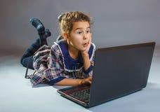Muchacha adolescente que juega en el piso en un gris del cuaderno Foto de archivo