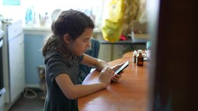 Muchacha adolescente que juega en el teléfono elegante en el juego online de la colegiala de la cocina metrajes