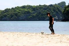 Muchacha adolescente que juega a fútbol en la playa blanca de la arena Foto de archivo libre de regalías