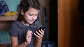 Muchacha adolescente que juega a juegos en línea de la escuela en su smartphone Imagen de archivo