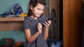 Muchacha adolescente que juega a juegos en línea de la escuela en su smartphone Fotos de archivo