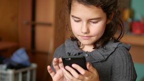 Muchacha adolescente que juega a los juegos onlines en su escuela del smartphone Fotografía de archivo