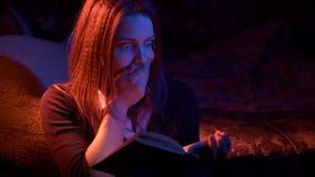 Muchacha adolescente que lee el libro asustadizo en la noche metrajes