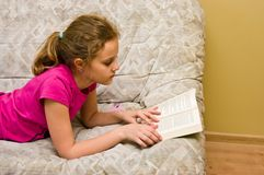 Muchacha adolescente que lee un libro en cama imagenes de archivo