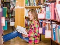 Muchacha adolescente que lee un libro en el piso en la biblioteca Fotos de archivo