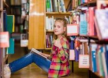 Muchacha adolescente que lee un libro en el piso en la biblioteca y que muestra los pulgares para arriba Foto de archivo libre de regalías