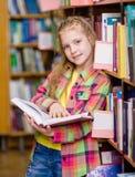 Muchacha adolescente que lee un libro en la biblioteca Fotos de archivo libres de regalías