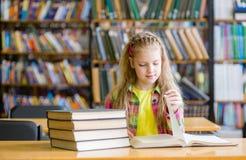 Muchacha adolescente que lee un libro en la biblioteca Imagen de archivo libre de regalías