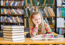 Muchacha adolescente que lee un libro en la biblioteca Fotografía de archivo