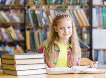 Muchacha adolescente que lee un libro en la biblioteca Imagenes de archivo
