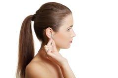 Muchacha adolescente que limpia un oído Foto de archivo