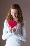 Muchacha adolescente que lleva a cabo corazones Foto de archivo