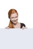 Muchacha adolescente que lleva a cabo una muestra con el copyspace para los anuncios Fotografía de archivo libre de regalías