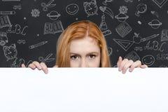 Muchacha adolescente que lleva a cabo una muestra con el copyspace para los anuncios Fotos de archivo libres de regalías