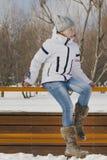 Muchacha adolescente que lleva la ropa caliente que camina afuera en el invierno, sentándose en el banco Imagenes de archivo