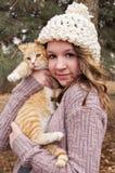 Muchacha adolescente que lleva un sombrero hecho a ganchillo que sostiene un retrato del gato Imagen de archivo libre de regalías