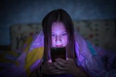Muchacha adolescente que miente en cama y que mira la pantalla que brilla intensamente del smartphone Foto de archivo libre de regalías