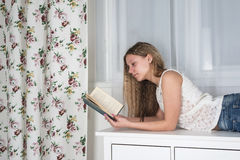 Muchacha adolescente que miente en el aparador y que lee un libro Imagen de archivo libre de regalías