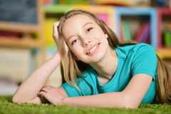 Muchacha adolescente que miente en la alfombra verde Imagenes de archivo