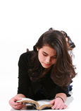 Muchacha adolescente que miente en la biblia de la lectura del suelo Fotos de archivo