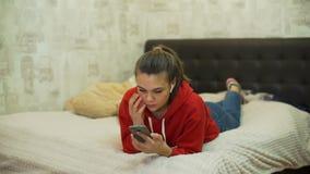 Muchacha adolescente que miente en la cama y el mensaje que mecanografía metrajes