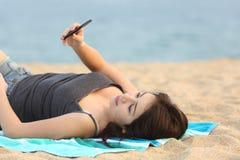 Muchacha adolescente que miente y que usa un teléfono elegante Imagenes de archivo