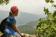 Muchacha adolescente que mira abajo de sentarse en el alto acantilado Foto de archivo libre de regalías