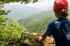Muchacha adolescente que mira abajo del alto acantilado Imagenes de archivo